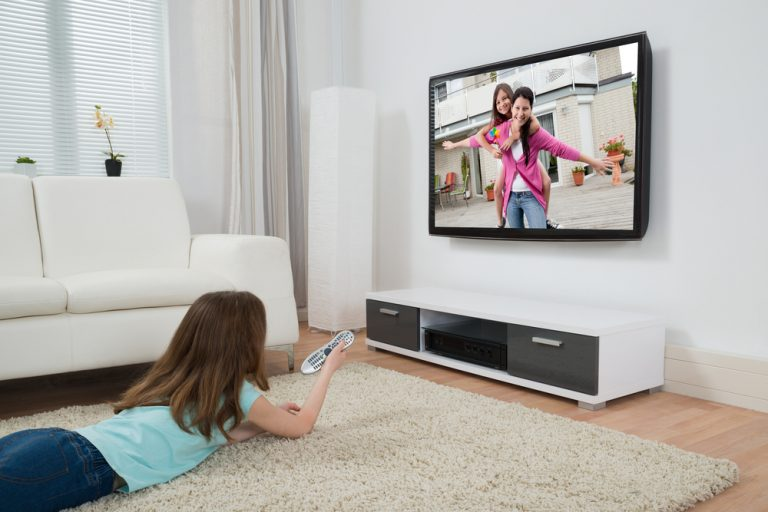 Girl watching wall mounted TV