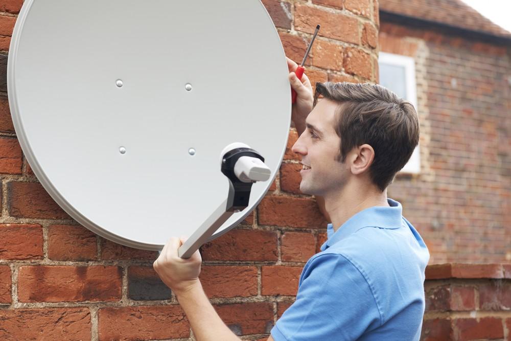 Man installing a satelite aerial to house